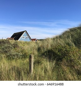 Beach houses in the dunes in a typical Dutch landscape on the island Vlieland at the Northern coast of Holland under blue skies