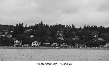 Beach houses on the pacific coast of Whidbey island on a grey day; black and white