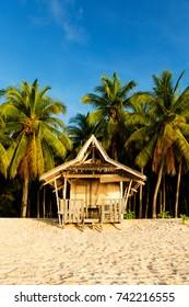 Beach hut on pristine tropical Philippine island at sunset