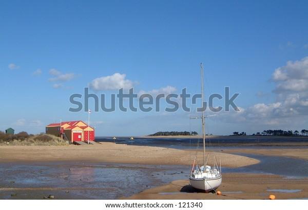 Beach hut sand sea shore sky clouds space trees sun boat sail