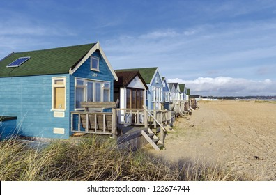 Beach huts and boats in sand dunes at Mudeford Spit on Hengistbury Head near Christchurch in Dorset.
