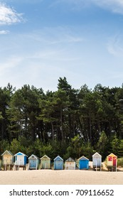 Beach huts line the bottom of this portrait crop on the edge of the beach at Wells Next The Sea on the North Norfolk coast.