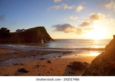 Beach huts on the cliff tops with the sun setting over Hope Cove, Devon, England