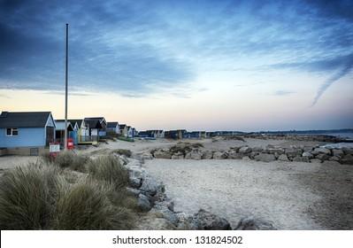Beach huts on Mudeford Spit at Hengistbury Head near Christchurch just after sunset.