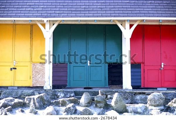 Beach huts with yellow, green and red colored doors