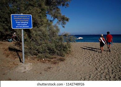 Beach information sign saying nudism and camping are for pleasure written in Greek and English in Anafi, Greece on Aug. 23, 2015