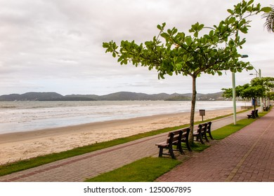 Beach of Itapema with bicycle lane, wooden benches and the Bombinhas region in the background, cloudy day, Santa Catarina