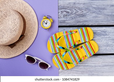 Beach items for resort flat lay. Top view, straw hat, alarm clock, sunglasses and flip-flops.