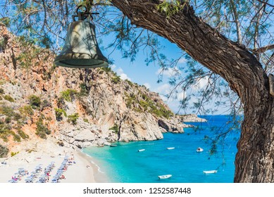 Beach of Karpathos island with a bell in a tree. Dodecanese, Greece.
