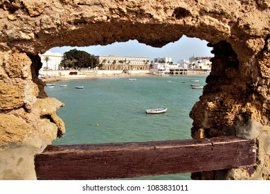 the beach of La Caleta de Cádiz, spain, seen from a hole in the wall of the fortress,