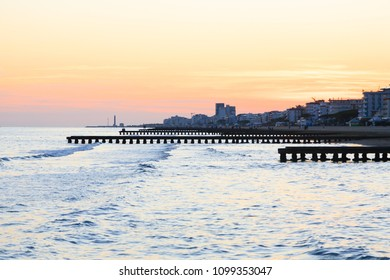 Beach landscape at dawn. Piers perspective view with people. Jesolo beach view, Italian panorama