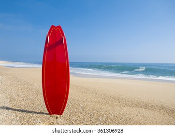 Beach landscape with a red surfboard on the sand