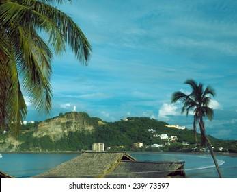 beach landscape resort town  San Juan del Sur Nicaragua with landmark statue Jesus Christ on mountain on Pacific Ocean Central America