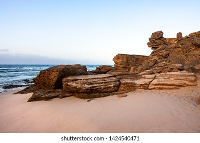 BEACH LANDSCAPE WITH ROCKS AND DAWN AT THE TRAFALGAR BEACH IN CADIZ, SPAIN