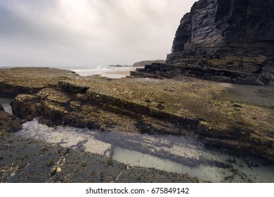 """Beach of """"Las Catedrales"""", in Gijon (Spain). Picture of black rocks and rocks covered with moss."""