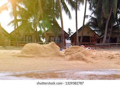 Beach leisure. Figures of a rabbit and a cat made of sand on the tropical beach. Palms and bungalows on background, wave and water at foreground.