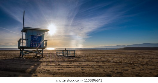 A beach life guard tower on a California beach at sunset.  The ocean, mountains and boats are in the background with a wonderful view of sand, sky and clouds.