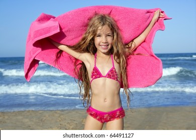 Beach little girl playing pink towel and wind in blue sea