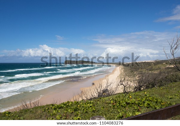 Beach lookout with waves and cars driving on the beach headland