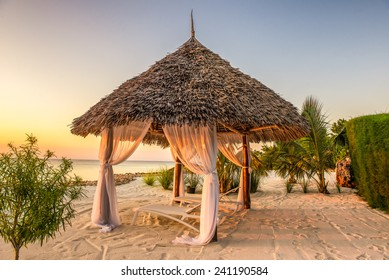 Beach lounge chairs at sunset at the shore of Indian ocean, Zanzibar, Tanzania