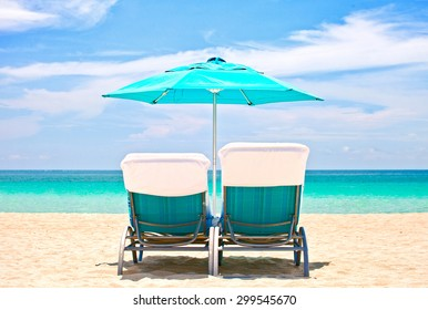 Beach lounge chairs and umbrella in Miami, Florida on a beautiful summer day with ocean and blue sky