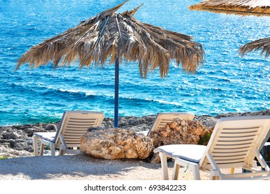 Beach lounge chairs under umbrella near azure sea. Vacation holidays background wallpaper