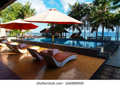 beach loungers and umbrellas at blue swimming pool beach Tropical vacations deck chairs resort landscape