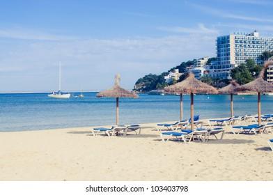 Beach loungers and umbrellas on the sea. Spain. Palma Mallorca