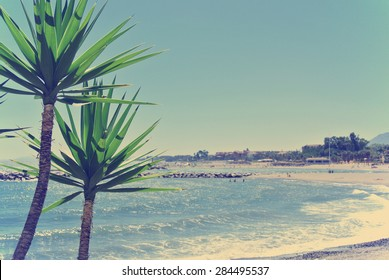 Beach in luxurious Spanish seaside resort Puerto Banus, located close to Marbella, on a sunny summer day. Filtered image in faded, washed-out, retro style; summer travel vintage concept.