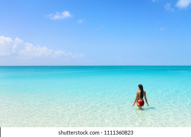 Beach luxury travel getaway resort bikini woman swimming in idyllic turquoise ocean water in paradise destination.