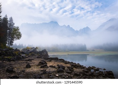 Beach with many rocks on lake Laghi di Fusine on a foggy morning with mountain range Mangart near Tarvisio in Italy, Europe