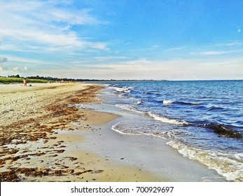 Beach in Marielyst, denmark with ocean waves of baltic sea and blue sky