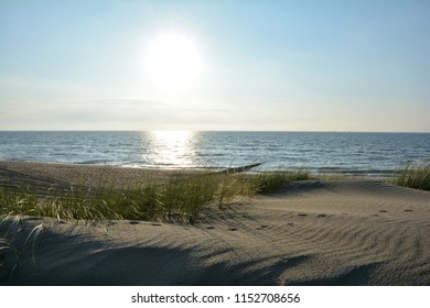 Beach with marsh grass and wooden stages on the North Sea at sunset