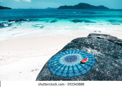 Beach mat with mandala pattern and watermelon slice on the tropical beach in summer sunny day. Holidays on the island and fruit diet.