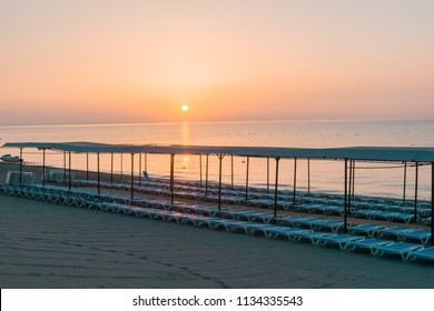 Beach in morning with sun loungers at sunrise