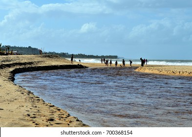 Beach of the Natives, Trancoso, Bahia, Brazil. July 29, 2017: People crossing the waters of the river Trancoso at its mouth.