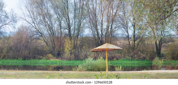 The beach near the autumn river. Umbrella on a deserted beach.