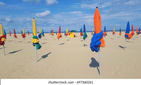 The beach near the boardwalk promenade with the famous colorful beach umbrellas at Deauville, Normandy, France