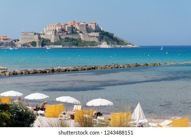 Beach near Calvi, Corse with white sunshades