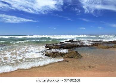 Beach near Mossel bay, South Africa with waves crashing on rocks under a cloudy sky.