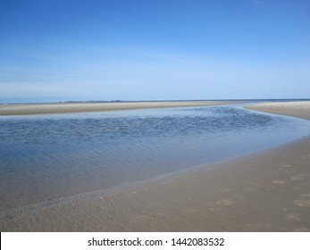 The beach at Norddorf on the island Amrum (Schleswig-Holstein, Germany) at low tide with ripples in the water. In the background the island of Sylt