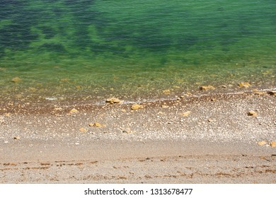 Beach in Normandy with transparent water during the summer in France. Seaweed and stony sand