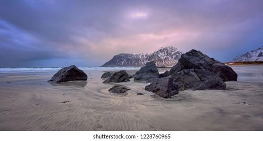 Beach of Norwegian sea on rocky coast in fjord on sunset. Skagsanden beach, Lofoten islands, Norway
