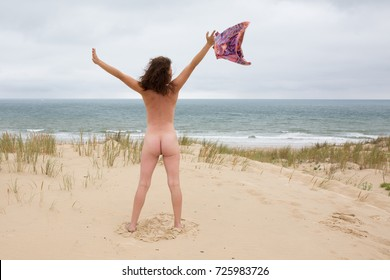 beach with nude lady. Woman with perfect figure shows her nude body