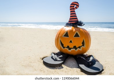 Beach and Ocean Happy Halloween background with pumpkin in the witch's hats and flip flops