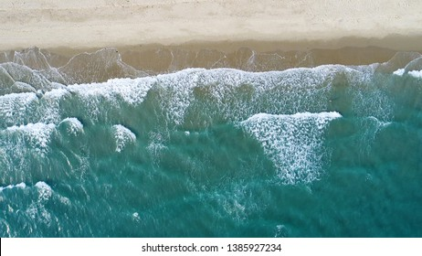Beach on aerial drone top view with ocean waves reaching shore.