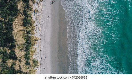 Beach on aerial drone top view with ocean waves reaching shore, op view aerial photo from flying drone of an amazingly beautiful sea landscape .