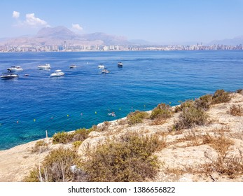 Beach on the island of Benidorm, Spain. Anchored boats near the island and with the bottom of the Benidorm skyline and the Mediterranean sea.