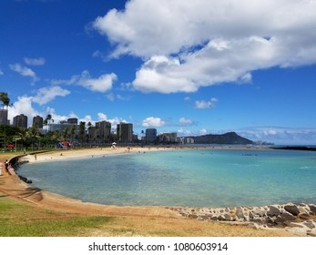 Beach on Magic Island in Ala Moana Beach Park on the island of Oahu, Hawaii.  Waikiki and Diamond Head in the distance and helicopter in the air on a beautiful day.
