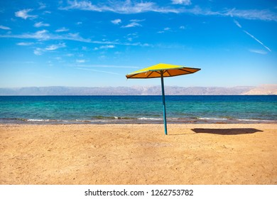 Beach on the shore of the Red Sea. Umbrella, water and beach. Resort in the Aqaba, Jordan near Israel Ejlat.